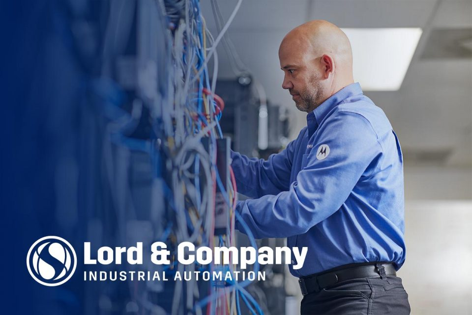 Male employee of Lord & Company adjusting a piece of automation equipment
