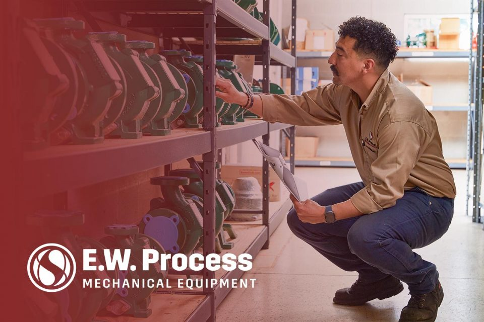 Male employee of E.W. Process looking at industrial pumps on a shelf