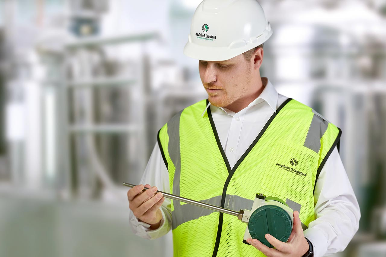Man in a processing plant wearing a hard hat holding a measurement instrument