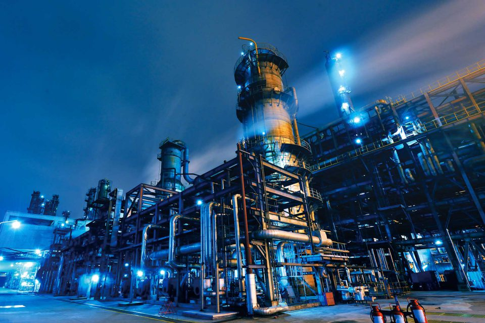 exterior of a chemical plant at night with blue lights