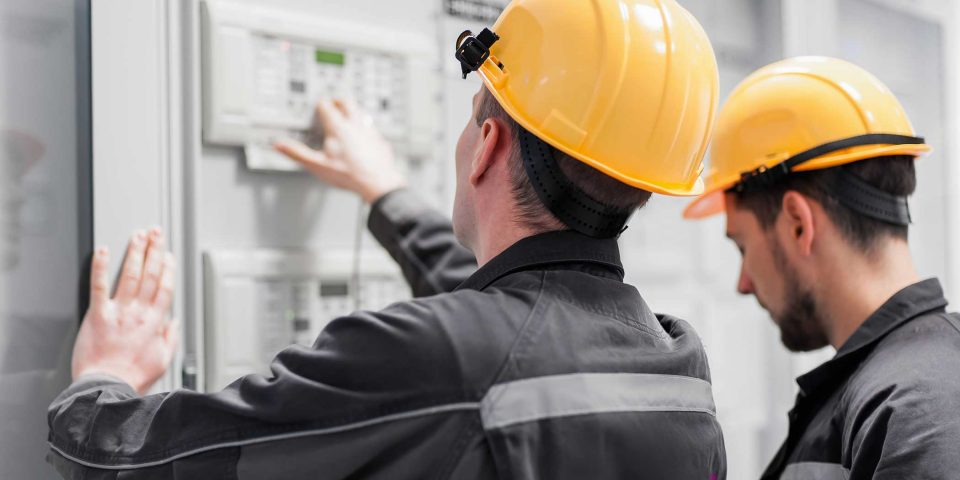Two Field service men in yellow hard hats inspecting indoor electrical installation system