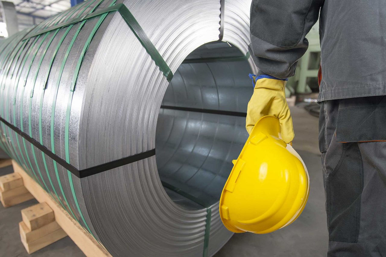 Worker with yellow protective helmet and protective gloves in front of tin metal rolls